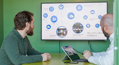 Twee collega's in een meeting die gebruik maken van een laptop die aangesloten is op een extra scherm.